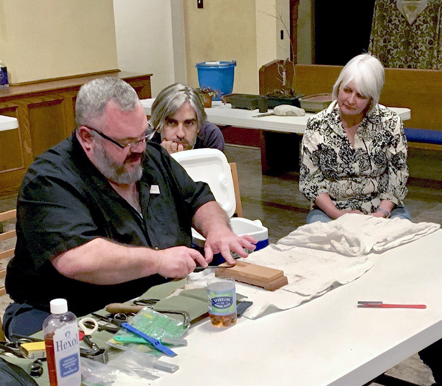 Jerry Carpenter demonstrating how to sharpen tools as club members look on
